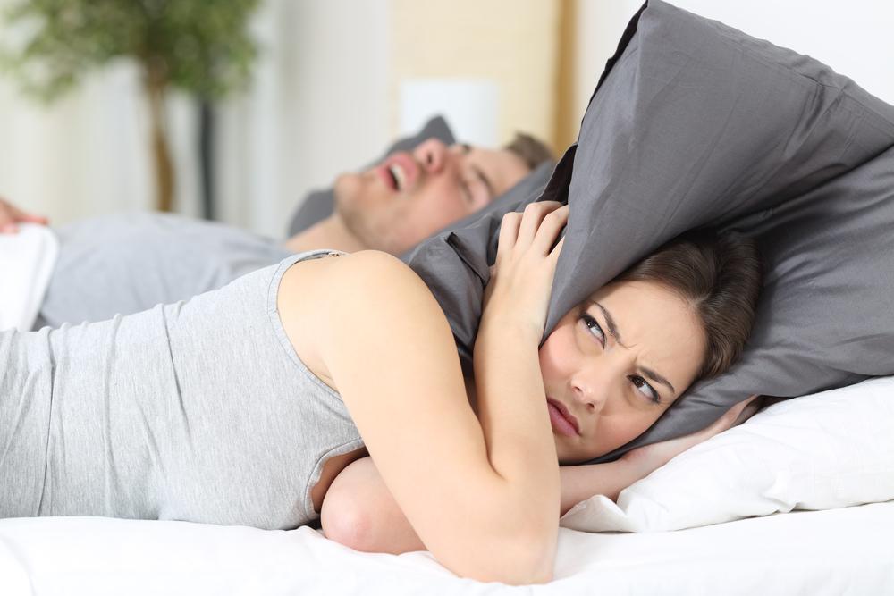 Mann schnarcht, Frau hält sich mit Kissen die Ohren zu